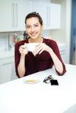 Vrolijke vrouw het drinken thee en het eten van koekje op de keuken Stock Afbeeldingen