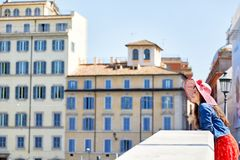 vrolijke vrouw in hoed die op leuning op brug in oude stad leunen Royalty-vrije Stock Foto