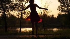 Vrolijke vrouw in lichte transparante en kleding zich dansen die omdraaien stock footage