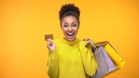 Vrolijke vrouw met het winkelen zakken en gouden creditcard, rijke klantenservice royalty-vrije stock fotografie