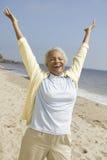 Vrolijke vrouw op middelbare leeftijd op strand stock afbeelding