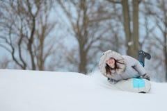 Vrolijke vrouw sleddind onderaan een heuvel; het slaan van de de winterblauw Stock Foto