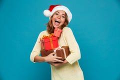 Vrolijke vrouw in sweater en Kerstmis de giftdozen van de hoedenholding Royalty-vrije Stock Afbeeldingen