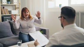 Vrolijke vrouwelijke geduldige zwaarlijvige vrouw die en tijdens therapie spreken lachen stock footage