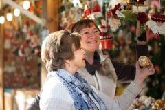 Vrolijke vrouwelijke gepensioneerden die Kerstmisdecoratie kopen bij markt Stock Afbeelding