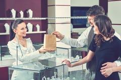 Vrolijke vrouwelijke juwelier die aankoop in een het winkelen zak overhandigen aan hij stock fotografie