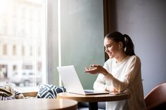 Vrolijke vrouwelijke ontwerper die webinar of online presentatie via notitieboekje hebben stock foto's