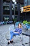 Vrolijke vrouwelijke persoonszitting als voorzitter met de bouw van achtergrond Royalty-vrije Stock Afbeeldingen