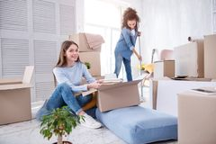 Vrolijke vrouwelijke studenten die en dorm ruimte uitpakken schoonmaken stock afbeelding