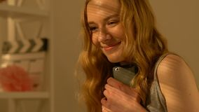 Vrolijke vrouwelijke tiener die met vriend op smartphone, eerste liefde babbelen stock footage