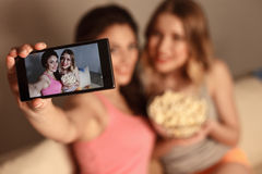 Vrolijke vrouwelijke vrienden die foto's van zich nemen stock foto's