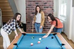 Vrolijke vrouwelijke vrienden die het biljartspel thuis spelen van de poollijst royalty-vrije stock foto's