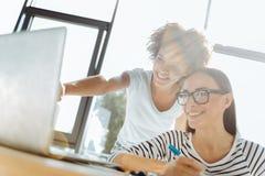 Vrolijke vrouwelijke vrienden die laptop samen met behulp van Stock Foto's