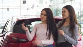 Vrolijke vrouwelijke vrienden die selfies dichtbij de nieuwe auto nemen stock footage