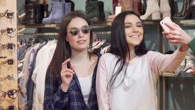 Vrolijke vrouwelijke vrienden die selfies met smartphone bij kledingsopslag nemen stock videobeelden