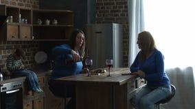 Vrolijke vrouwelijke vrienden die vrije tijd in keuken besteden stock video