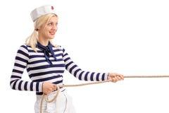 Vrolijke vrouwelijke zeeman die een kabel trekken Stock Foto's