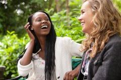 Vrolijke vrouwen die van praatje in het park genieten stock foto's