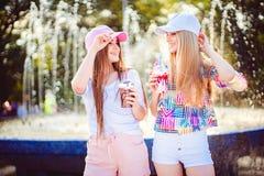Vrolijke vrouwen met dranken dichtbij fontein royalty-vrije stock afbeeldingen