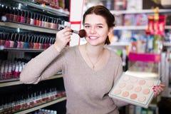 Vrolijke vrouwenklant die over compact poeder in winkel beslissen stock foto