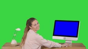 Vrolijke vrouwenzitting bij de lijst met een computer in bureau en het bekijken camera die Blue Screen-Prototypevertoning glimlac stock video
