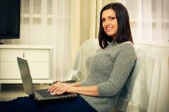 Vrolijke vrouwenzitting op de vloer met laptop Stock Foto's