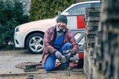 Vrolijke werkman die het bedekken bakstenen in de winter leggen Stock Afbeelding