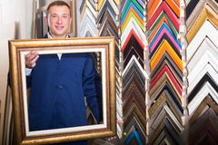Vrolijke werkman die houten beeld ontwerpend afgietsel houden Stock Fotografie