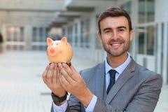 Vrolijke zakenman die een piggybank houden Royalty-vrije Stock Fotografie