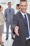 Vrolijke zakenman die introduceren die zijn hand standhouden Royalty-vrije Stock Foto's