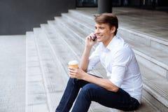 Vrolijke zakenman met kop die van koffie op mobiele telefoon spreken stock afbeelding
