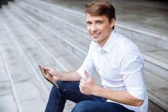 Vrolijke zakenmanzitting en in openlucht het gebruiken van tablet stock afbeelding