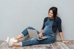 Vrolijke zwangere damezitting op vloer die laptop computer met behulp van stock afbeelding