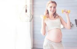 Vrolijke zwangere vrouw die sportoefeningen doen Stock Afbeelding
