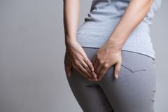 Vrouw aan hemorroïden lijden en hand die haar bodem houden omdat hebbend Buikpijn Het concept van de gezondheidszorg stock afbeelding