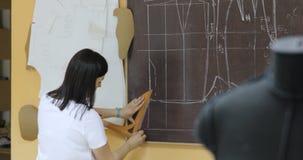 Vrouw aan het werk als manierontwerper en kleermaker, die schetsen in atelier bekijken stock video