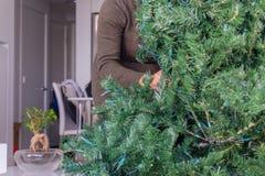 Vrouw achter een kunstmatige Kerstboom royalty-vrije stock afbeeldingen