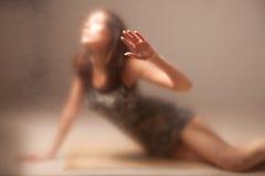 Vrouw achter glas. Stock Afbeeldingen