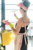 Vrouw als gezinshulp bij de lente het schone werken aan de vensters royalty-vrije stock afbeeldingen