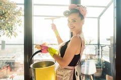 Vrouw als gezinshulp bij de lente het schone werken aan de vensters royalty-vrije stock afbeelding