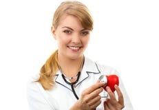 Vrouw arts die met stethoscoop rood hart, gezondheidszorgconcept onderzoeken royalty-vrije stock foto's