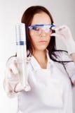 Vrouw arts in glazen met een spuit Royalty-vrije Stock Afbeeldingen