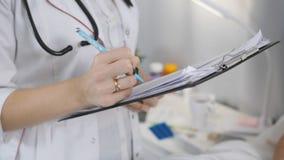 Vrouw arts in het ziekenhuisafdeling die aan een patiënt spreken die in bed liggen, en nota's, close-up nemen stock footage