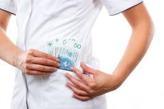 Vrouw arts met het geld van de poetsmiddelmunt in schort zak, corruptie, steekpenning of het betalen voor zorgconcept stock fotografie