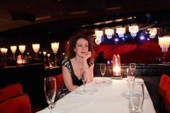 Vrouw in avondjurkzitting bij lijst Royalty-vrije Stock Afbeeldingen