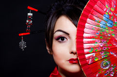 Vrouw in Aziatisch kostuum met rode Aziatische ventilator Stock Foto