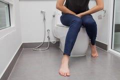 Vrouw in badhanddoekzitting op toiletkom Royalty-vrije Stock Fotografie