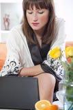 Vrouw in badjas met computer Royalty-vrije Stock Afbeeldingen