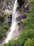 Vrouw in badpak die zich onder een waterval bevinden Stock Afbeeldingen