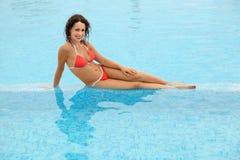 Vrouw in badpakzitting in pool stock afbeeldingen